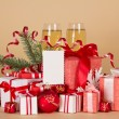 Christmas gifts and toys, pine branch with a serpentine, champagne and an empty card on a beige background — Stock Photo