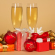 Set of different gift boxes, toys, a snowflake and wine glasses with champagne on a beige background — Stock Photo
