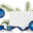 Fir-tree branch with bright toys, serpentine, souvenirs and a card isolated on white — Stock Photo