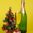 Champagne, small fir-tree in a pot, and a gift box on a yellow background — Stock Photo
