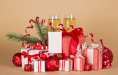 Christmas gifts and toys, pine branch with a serpentine, champagne and an empty card on a beige background — Foto Stock