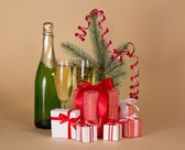 Fir-tree branch, bottle and wine glasses with champagne, big and small gift boxes on a beige background — Stock Photo