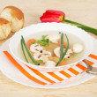 Plate with soup on a dish with a striped napkin, a spoon, bread and a red tulip — Stock Photo #32289973