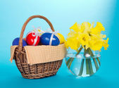 Easter eggs in a basket with a napkin and a vase with narcissuses, on the blue — Stock Photo