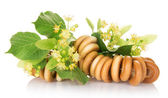 The bagels connected by a rope, and linden flowers, isolated on white — Stock Photo