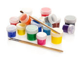 Paint in the jars, randomly standing and the brushes isolated on white — Stock Photo