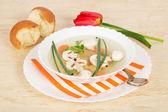 Plaat met soep op een schotel met een gestreepte servet, een lepel, brood en een rode tulp — Stockfoto