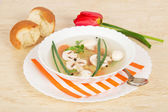 Placa con sopa en un plato con una servilleta rayada, una cuchara, pan y un tulipán rojo — Foto de Stock