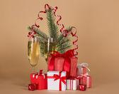 Spar-tree branch, wijn glazen met champagne, grote en kleine geschenkdozen op een beige achtergrond — Stockfoto