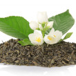 Heap of dry tea with a green leaf and flowers of the jasmine, isolated on white — Stock Photo