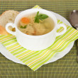 Bowl with soup, bread, a plate, a spoon and a napkin on a green bamboo cloth — Stock Photo #32290611