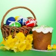 Yellow narcissuses, Easter cake, marzipan chickens and eggs in a basket, on a green background — Stock Photo #32291055