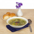Vase with violets, a plate of vegetable soup, a spoon and a saucer with pies on a table — Stock Photo #32291385