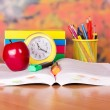 The open book, big red apple, a alarm clock and school accessories on a table — Foto de Stock