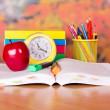 le livre ouvert, grosse pomme rouge, un radio-réveil et des accessoires d'école sur une table — Photo