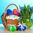 Easter cake, basket with eggs, a vase with the flowers on a table, on a blue background — Stock Photo