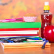 A set of school accessories, bottle with drink, cake and apple, on a table — Stock Photo