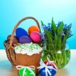 Easter cake and eggs in a basket, a vase with the flowers on a table, on a blue background — Foto de Stock
