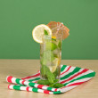 Stock Photo: Mojito decorated with umbrelland lemon, mint, striped napkin on table