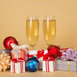 Set of different gift boxes, toys and wine glasses with champagne on a beige background — Stock Photo