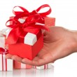 A lot of gift boxes and woman's hand holding a gift isolated on white — Stock Photo