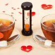 Two hot teas and hourglasses on a cloth decorated with hearts — Stock Photo