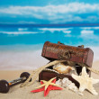 Ancient chest with sea cockleshells, hourglasses and a rope on sand — Stock Photo #32293927