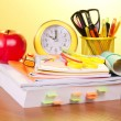 The book, a roll of exercise books, a support with handles, an alarm clock and red apple — Stockfoto