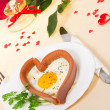 Festive a breakfast on Valentine's Day, sausage in the form of heart, fried egg, bread, red rose, bottle of perfume with red ribbon on tablecloth, isolated on white — Stock Photo