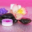 Candle and aroma oil, salt, stones and a flower — Stock Photo