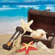 Ancient chest with sea cockleshells, hourglasses and a rope on sand — Stock Photo #32294427