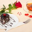 Chocolate cake, hot tea and red rose on a cloth decorated with hearts in Valentine's day — Stock Photo