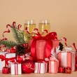 Gift boxes, Christmas toys, pine cones, serpentine and wine glasses with champagne on a beige background — Photo