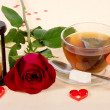 Hot tea, red rose and hourglasses on a cloth decorated with hearts — Stock Photo #32294923