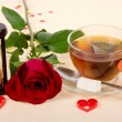 Hot tea, red rose and hourglasses on a cloth decorated with hearts — Stock Photo