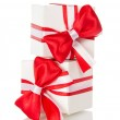 Two white gift boxes with a red bow and the tape — Stock Photo #32295243