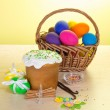 Easter cake, basket with eggs, vanilla and cinnamon, on a table on a yellow background — Stock Photo