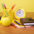 Exercise book, organizer, a support with handles, apple and an alarm clock — Stock Photo