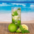 Glass with a mojito, a juicy lime and a spearmint leaf, on a bamboo cloth against the sea — Stock Photo