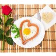 Sausage in the form of heart on a white plate, scrambled eggs and bread, red rose isolated on white — Stock Photo