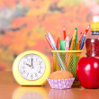 Alarm clock, stand with pencils and handles, a cake, drink and apple on a table — Stock Photo