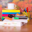 Books, cup with a saucer and writing-materials on a table — Stock Photo #32296901