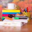 Books, cup with a saucer and writing-materials on a table — Stock Photo