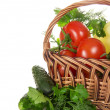 Tomatoes and pepper in a basket, nearby a cucumber and the greens — Stock Photo