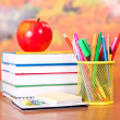 Books, apple, pencils and handles in a support and empty cards, on a table — Stock Photo