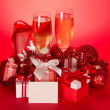 Wine glasses with champagne, gift boxes, Christmas spheres, tinsel and blank card on a red background — Stock Photo