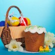 Eggs in a basket, an Easter cake, marzipan chickens and a bouquet of white narcissuses, on the blue — Stock Photo