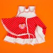 Children's dress, kerchief and pacifier, on an orange background — Stock Photo