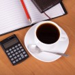 Open notepad, a pencil, the calculator, cup of coffee, saucer and spoon on a table — Stock Photo