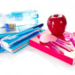 Books, a notepad, a set of stationery, apple and a bottle with the water — Stock Photo #32297471